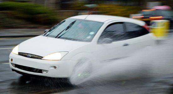 Voiture qui fait de l'aquaplaning sur une route mouillée sous la pluie