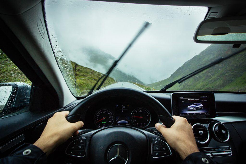 Conducteur au volant de sa voiture sous la pluie