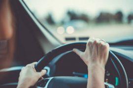 Mains de femme sur un volant de voiture